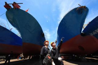 Two surveyors inspect ships