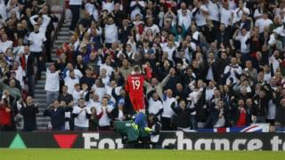 Wayne Rooney celebrates in front of England football fans