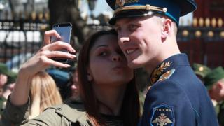 A woman takes a selfie with a Russia soldier