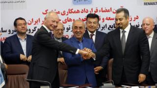 Thierry Bollore (L), deputy director in Competitiveness at Renault Group and Mansour Moazami (C) Chairman of the Board of Directors of IDRO Group, and Kourosh Morshed Solouki (R), deputy director of the Iranian Automobile Importers Association shake hands as Commerce Minister Mohammad Reza Nematzadeh (2-L back), looks on after during signing documents in Tehran, Iran, 07 August 2017.