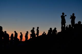 Silhouettes of people watching a sunset atop the Aeropagus hill in Athens