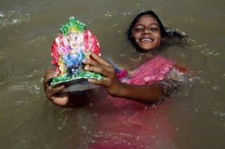 An Indian girl carries an idol of the elephant-headed Hindu god Lord Ganesha.