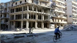 A man rides a bicycle near damaged buildings in the rebel held besieged al-Sukkari neighbourhood of Aleppo, Syria on 19 October 2016.