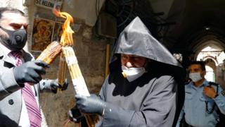 An Armenian priest wearing a protective mask and gloves passes on the Holy Fire lit in the church of the Holy Sepulchre