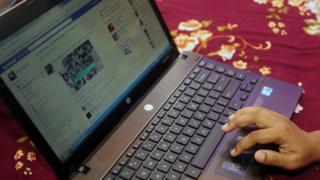 A Bangladeshi woman logging onto Facebook on a laptop