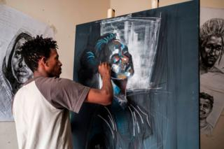 A man uses coloured paint and chalk on a dark canvas.