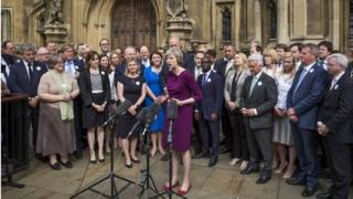 Theresa May talks outside the Houses of Parliament surrounded by supporting MPs