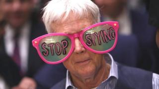 """一名示威者戴上""""停止间谍行为""""眼镜"""