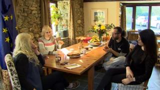 Four people sitting around a table talking