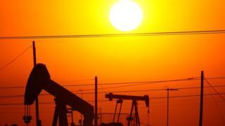 Imagem alaranjada de um pôr-do-Sol por trás de uma instalação petrolífera