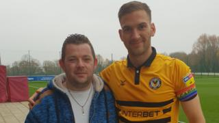 Newport County fan Adam Smith pictured with club captain Mickey Demetriou