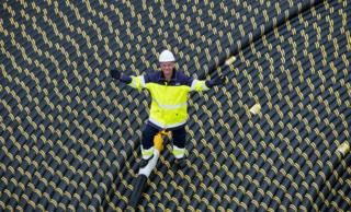 Worker standing on coil of subsea cable