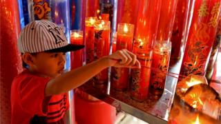 A child burns incense sticks and prays in Indonesia.