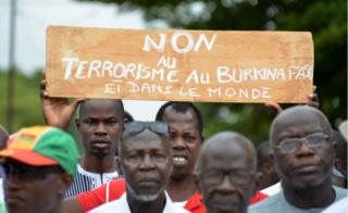 "Protestors march holding a placard they take part in a rally ""no to barbarism"" in central Ouagadougou on August 19, 2017, after a recent attack in the capital of Burkina Faso in which 18 people were killed. Gunmen killed nine locals and nine foreigners as they dined on the terrace of a Turkish restaurant in Ouagadougou late August 13."