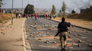 A member of the Metropolitan Police watches a mob of rioters in Johannesburg earlier this month