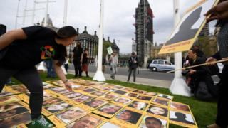 Campaigners display photos of the victims of the Grenfell Tower fire outside the Houses of Parliament