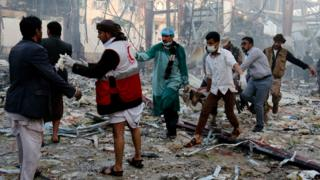 медики уносят убитого в результате авиаудара