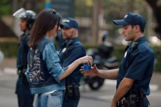 Kendall Jenner gives drink to officer