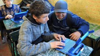 Dos adolescentes trabajan con una computadora.