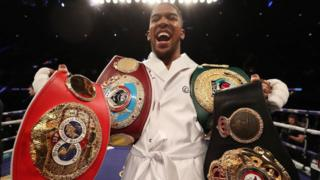 Anthony Joshua with four heavyweight title belts.