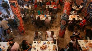 People eat their Iftar (breaking of fast) meal at tables offering free food, set up by a charity, during the holy fasting month of Ramadan in Benghazi, Libya, June 29, 2016.