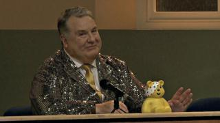 A picture of Russell Grant in a gold jacket