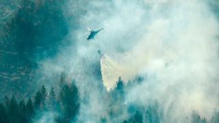 Firefighters use a helicopter to tackle a forest fire burning near Ljusdal, Sweden on July 18, 2018