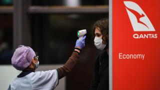 Passengers have their temperature checked by health officials as they arrive from a Qantas flight at Sydney Airport.
