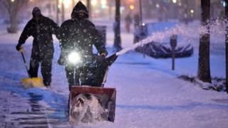 Workers clean the snow from a street in Washington DC.
