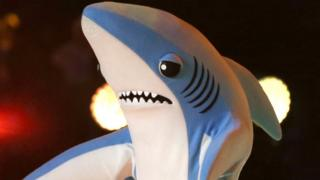 Katy Perry singing at the Superbowl flanked by people dressed as sharks