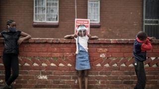 Children keep safe distancing as they queue at a food distribution organised by the grassroots charity Hunger Has No Religion, in Westbury, Johannesburg, on May 19, 2020.