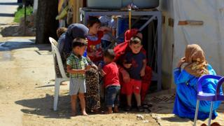 Syrian refugees sit with their children outside tents at a camp in the eastern Lebanese town of Saadnayel (19 July 2016)