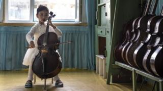 朝鲜咸镜北道清津的一家幼儿园里,一名女孩正在演奏大提琴。