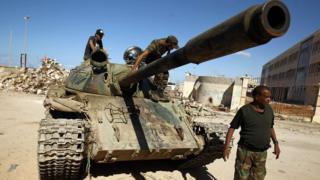 A picture taken on 9 November 2017 shows members of the self-styled Libyan National Army, loyal to the country's east strongman Khalifa Haftar, riding on a tank as it drives down a street in Benghazi