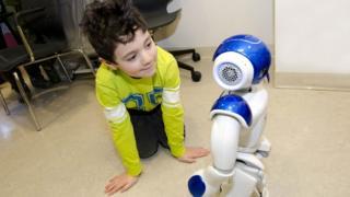 Menino ajoelhado e interagindo com o robô MEDi