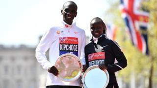 Eliud Kipchoge and Vivian Cheruiyot of Kenya pose as they receive their trophies, following their first place results during the Virgin Money London Marathon on 22 April 2018
