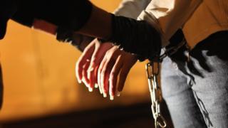Una mujer que deportan de Estados Unidos es esposada por las autoridades.