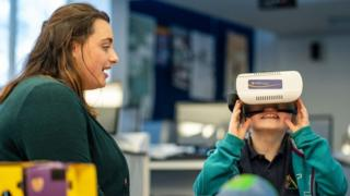 Carys Huntly with a female student testing a VR headset