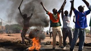 Demonstrators shout slogans next to burning tyres in the Tampouy neighbourhood of Ouagadougou during a protest against a regional proposal to end the crisis in Burkina Faso on September 21, 2015