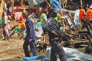 Security officers secure the scene of a suicide car bomb attack in Somalia's restive capital, Mogadishu, on November 26, 2016.