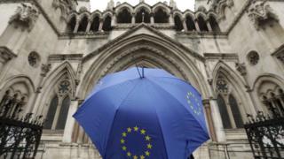 Guarda-chuva com logo da União Europeia em frente ao prédio da Alta Corte, em Londres