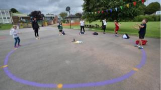 Children dance on a measured and painted socially distanced circle in the playground as they wait to be picked up by their parents at Llanishen Fach Primary School in Cardiff