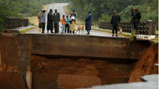 In Chimanimani, Zimbabwe, locals overlook an entire bridge that has been washed away.