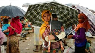 Rohingya refugees stand in heavy rain as they are held by the Border Guard Bangladesh (BGB) in an open area after illegally crossing the border, in Teknaf