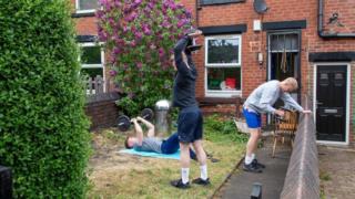 Men use gym equipment in a garden