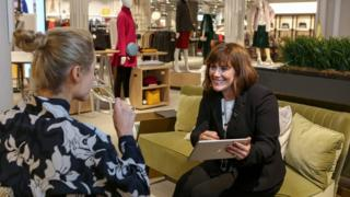 A woman drinks champagne while a personal shopper assists her