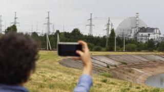Un visitante toma fotografías del Nuevo Confinamiento Seguro que cubre el cuarto reactor de la planta nuclear de Chernóbil
