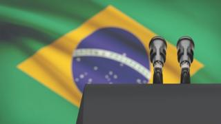 Púlpito com microfone e bandeira do Brasil ao fundo