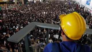 Anti-extradition bill protesters attend a mass demonstration after a woman was shot in the eye during a protest at Hong Kong International Airport, i