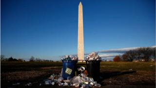 Trash begins to accumulate along the National Mall near the Washington Monument due to a partial shutdown of the federal government